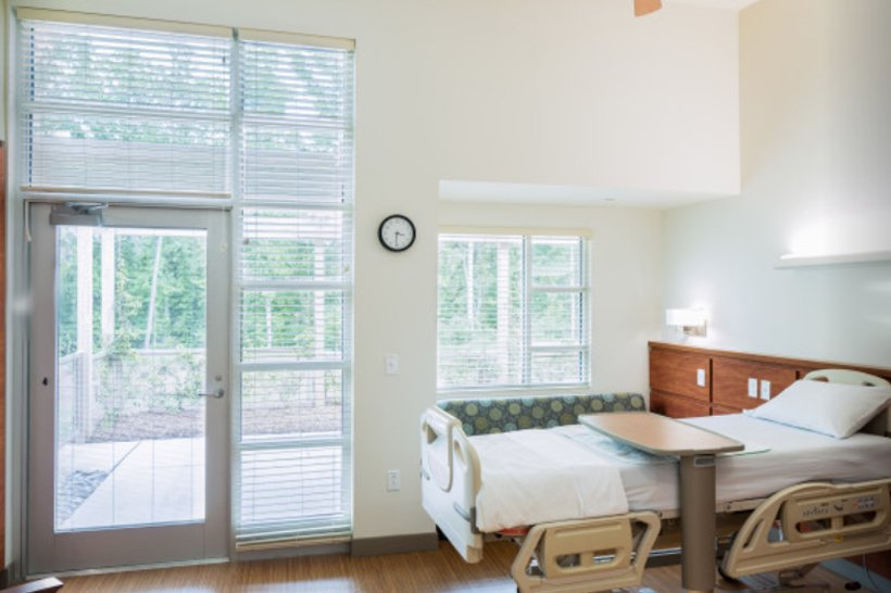 NC Hospice House patient room with window, comfortable seating and bed
